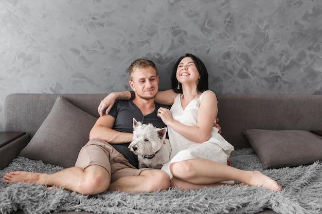 Glückliche junge paare, die auf sofa mit weißem hund sitzen