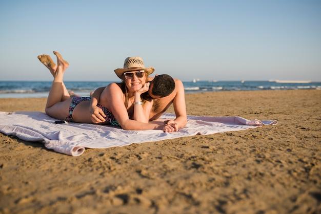 Glückliche junge paare, die auf teppich auf sandigem strand im sommer liegen