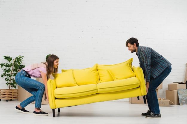Glückliche junge paare, die das gelbe sofa in das wohnzimmer setzen