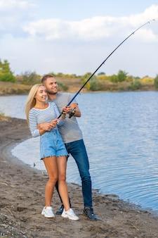 Glückliche junge paare, die durch seeufer fischen