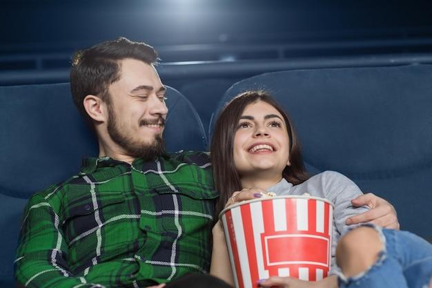 Glückliche junge paare, die ein datum am kino haben