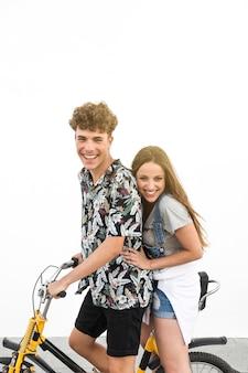 Glückliche junge paare, die fahrt auf fahrrad gegen weißen hintergrund genießen