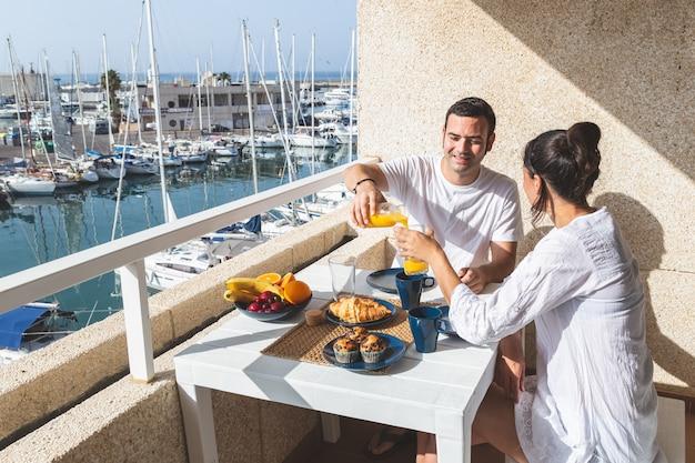 Glückliche junge paare, die frühstück auf der terrasse genießen