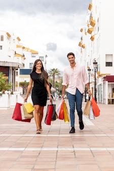 Glückliche junge paare, die mit einkaufstaschen gehen