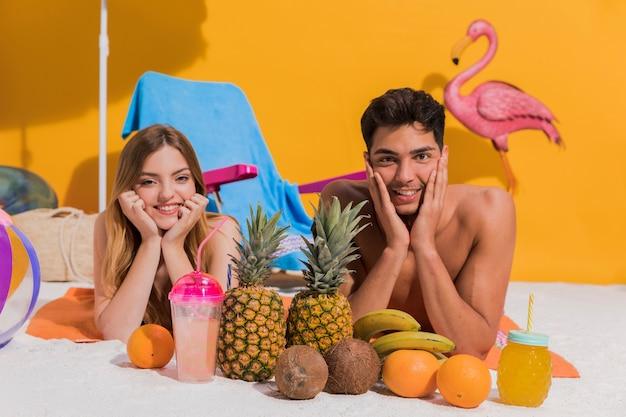 Glückliche junge paare, die mit frucht auf strand im studio liegen