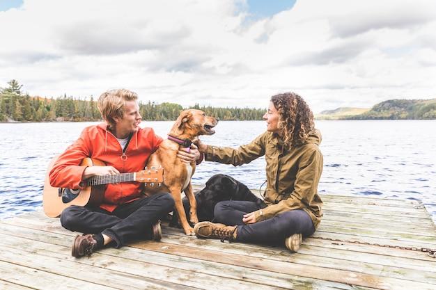 Glückliche junge paare, die mit hund auf einem dock spielen