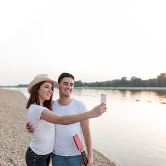 Glückliche junge paare, die selfies bei sonnenuntergang nehmen
