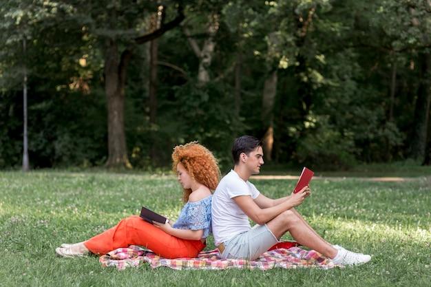 Glückliche junge paare, die zurück zu rückseite auf einer picknickdecke sitzen