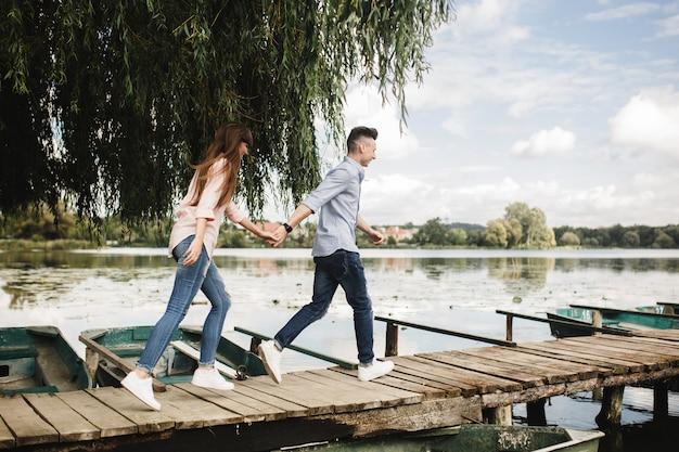 Glückliche junge paare draußen. junge liebespaare, die entlang händchenhalten einer holzbrücke laufen.