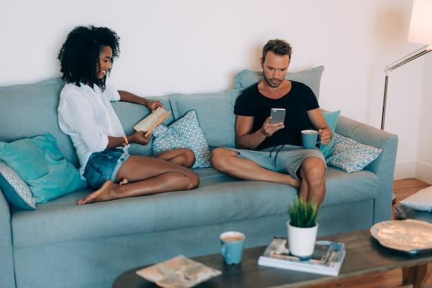Glückliche junge paare entspannten sich zu hause in der couch, die ein buch liest und den handy betrachtet