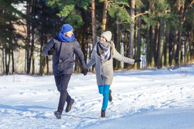 Glückliche junge paare im winter-park, der spaß lacht und hat