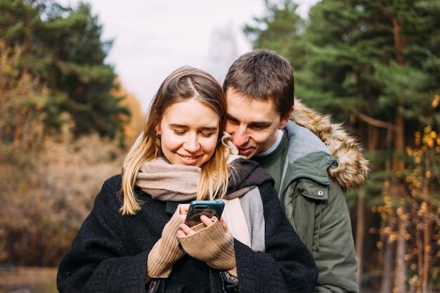 Glückliche junge paare in den liebesfreundreisenden kleideten in der zufälligen art unter verwendung des mobiles auf naturparkwald an