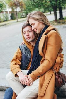 Glückliche junge paare in den liebesjugendlichfreunden kleideten im zufälligen auf der stadtstraße in der kalten jahreszeit zusammen sitzen an