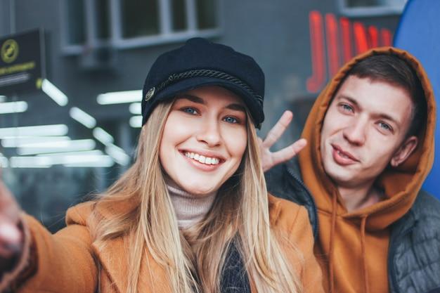 Glückliche junge paare in den liebesjugendlichfreunden kleideten in der zufälligen art an, die selfie auf stadtstraße in der kalten jahreszeit macht