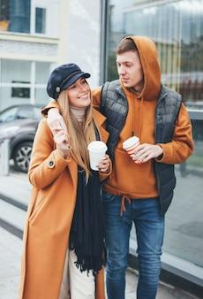 Glückliche junge paare in den liebesjugendlichfreunden kleideten in der zufälligen art an, die zusammen auf stadtstraße in der kalten jahreszeit geht