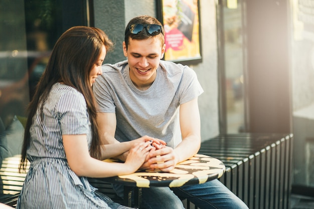 Glückliche junge paare in den liebesjugendlichfreunden kleideten in der zufälligen art an, die zusammen sitzt
