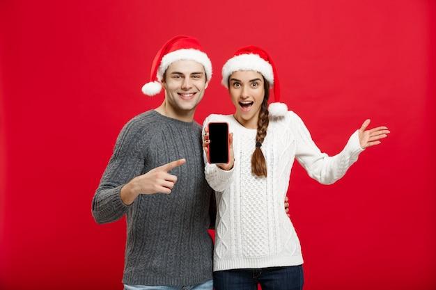 Glückliche junge paare in den weihnachtsstrickjacken, die finger mit handy zeigen.