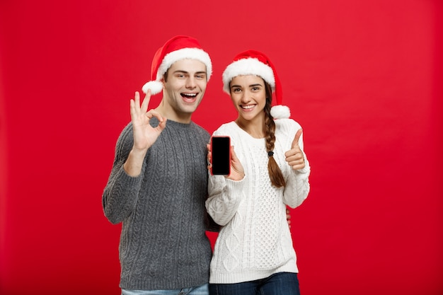 Glückliche junge paare in den weihnachtsstrickjacken, die okaygeste mit handy zeigen.