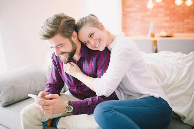 Glückliche junge paare mit telefon auf couch