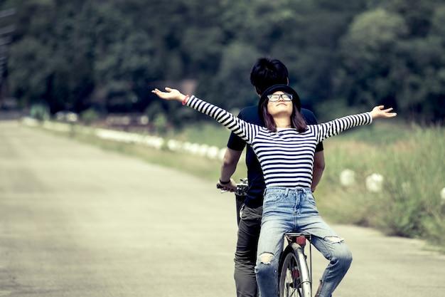 Glückliche junge paare von den hippies, die zusammen fahrrad im weinlesefarbton fahren