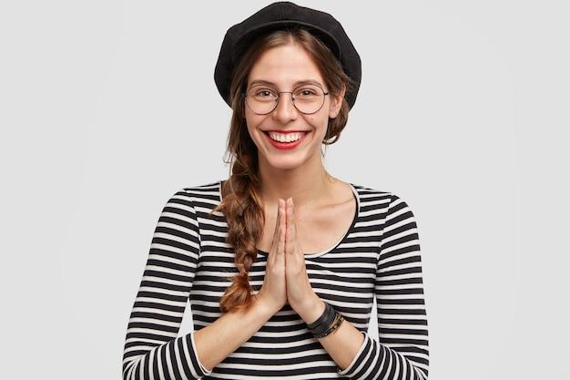 Glückliche junge pariser frau mit fröhlichem ausdruck