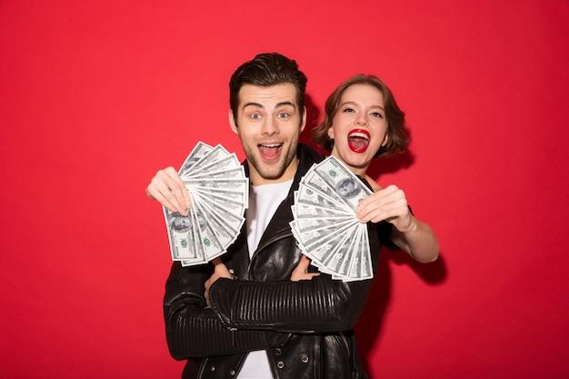 Glückliche junge punkpaare, die mit geld aufwerfen