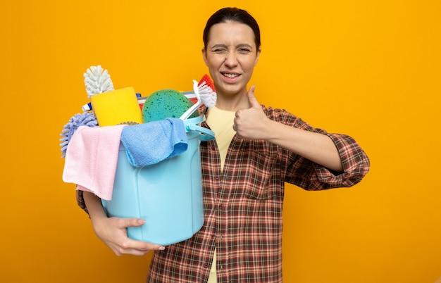 Glückliche junge putzfrau im karierten hemd, die einen eimer mit reinigungswerkzeugen hält und lächelt und zwinkert mit daumen nach oben stehend auf orange