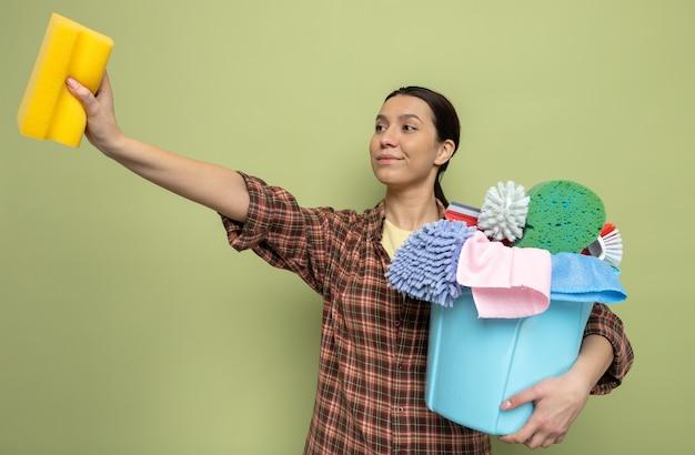 Glückliche junge putzfrau im karierten hemd, die schwamm und eimer mit reinigungswerkzeugen hält und beiseite lächelt, zuversichtlich, auf grün stehend