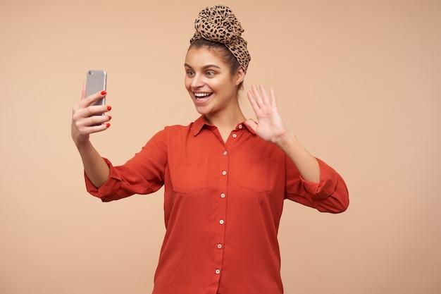 Glückliche junge reizende braunhaarige frau mit dem stirnband, das fröhlich vor ihrem telefon lächelt und hand in hallo geste anhebt, während videoanruf hat, der über beige wand aufwirft