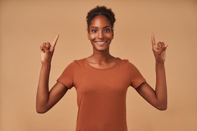 Glückliche junge reizende dunkelhäutige brünette frau, die ihre hände erhoben hält, während sie nach oben zeigt und breit lächelt und auf beige steht