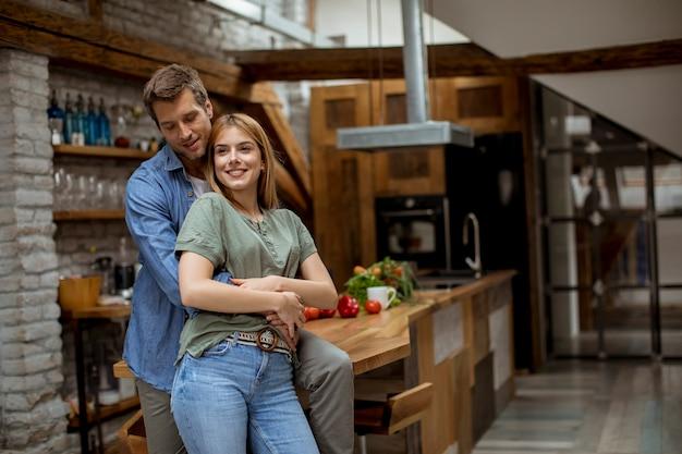 Glückliche junge reizende paare in der küche, die sich umarmt