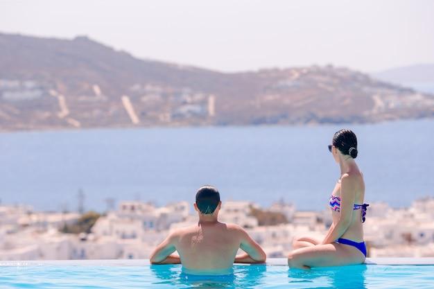 Glückliche junge romantische paare, die am rand des swimmingpools sich entspannen