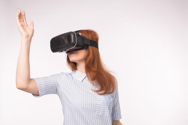 Glückliche junge rothaarige frau, die ein virtual-reality-headset verwendet