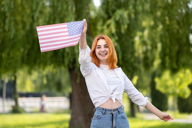 Glückliche junge rothaarige frau, die usa-nationalflagge in ihren händen draußen im sommer hält