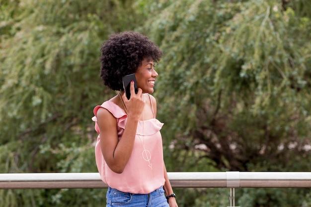 Glückliche junge schöne afroamerikanische frau, die lächelt und handy benutzt. grüner hintergrund. frühlings- oder sommersaison. freizeitkleidung im freien