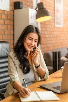 Glückliche junge schöne asiatische geschäftsfrau, die das telefon annimmt, während sie einen computer während der arbeit von ihrem hauptbüro während covid pandamic lockdown, vertikales porträtformat verwendet