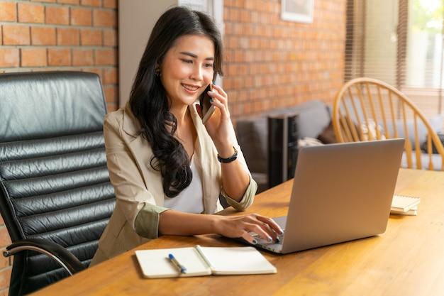 Glückliche junge schöne asiatische geschäftsfrau, die das telefon annimmt, während sie einen computer während der arbeit von ihrem hauptbüro während covid pandamic lockdown verwendet