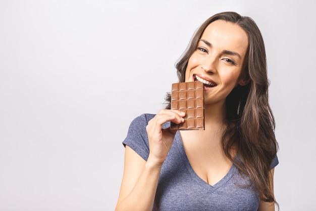 Glückliche junge schöne dame, die schokolade isst und lächelt