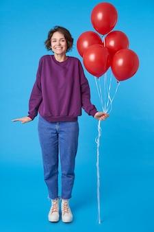 Glückliche junge schöne dunkelhaarige frau, die bündel der roten luftballons hält
