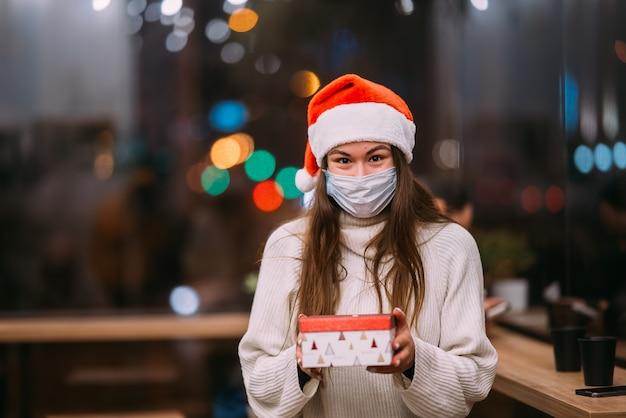 Glückliche junge schöne frau des porträts halten geschenkbox und lächeln im café