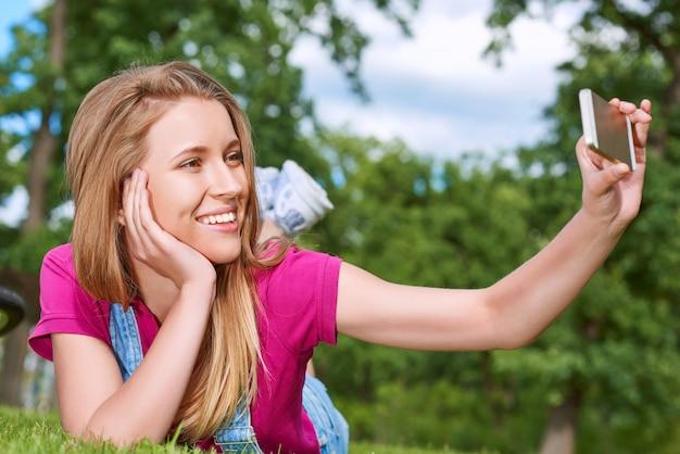 Glückliche junge schöne frau, die lächelt, während sie ein selfie mit ihrem smartphone nimmt, das auf frischem grünem gras am parktechnologie-mobilitätskommunikationsmobilitäts-3g 4g internet-webkonzept liegt.