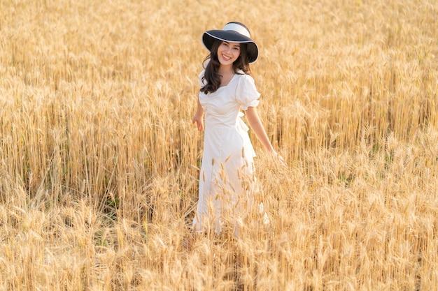 Glückliche junge schöne frau, die schwarzen hut und weißes kleid trägt und sich amüsiert, in der goldenen gerste spazieren zu gehen, die an einem späten nachmittag abgelegt wurde