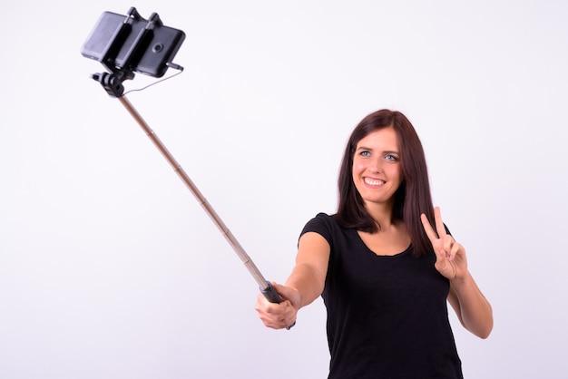 Glückliche junge schöne frau, die selfie mit telefon auf selfie stock nimmt