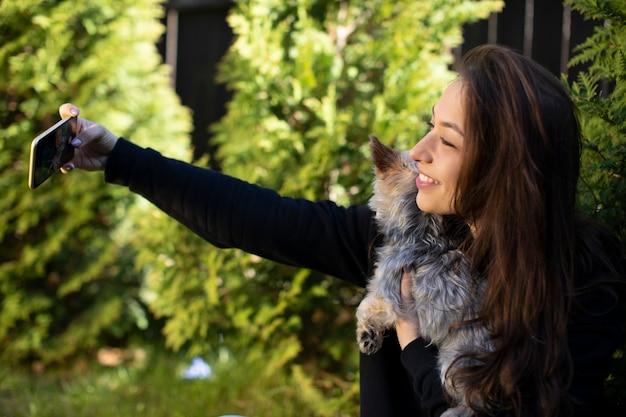 Glückliche junge schöne frau, die spaß im freien hat und selfie auf handy mit kleinem haustierhund macht