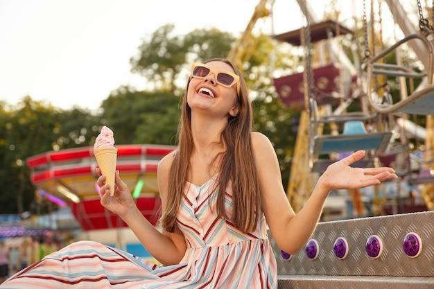 Glückliche junge schöne frau im romantischen hellen kleid, das über vergnügungsparkdekorationen mit eistüte in der hand sitzt, mit geschlossenen augen lächelt und handfläche anhebt