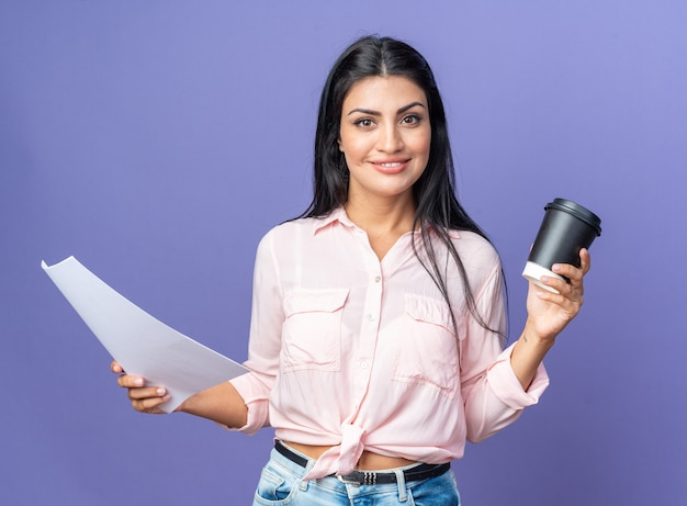 Glückliche junge schöne frau in freizeitkleidung, die dokument und kaffeetasse hält und selbstbewusst lächelt