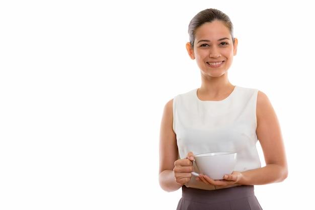 Glückliche junge schöne frau lächelnd und kaffeetasse haltend