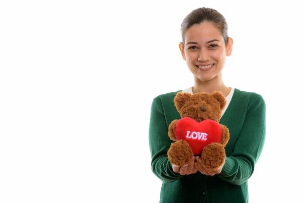 Glückliche junge schöne frau lächelnd, während sie einen teddybär hält