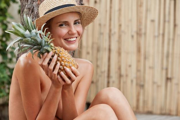Glückliche junge schöne frau mit breitem warmem lächeln und attraktivem blick, genießt gesunde vegetarische ernährung, hat sommerstimmung.