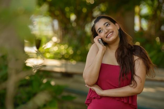 Glückliche junge schöne indische frau, die am telefon am park spricht